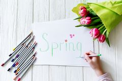 School supplies for drawing on the desk: paper and crayons. The child holds a pencil in his hands and writes the word `Spring` royalty free stock photography