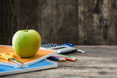 School supplies and green apple on rustic wooden background Royalty Free Stock Photos