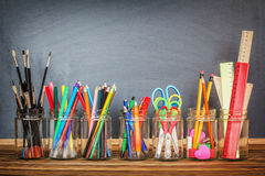 School supplies in jars. Against the blackboard Stock Photos