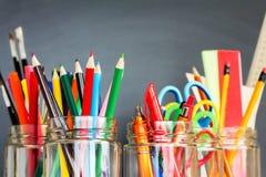 School supplies in jars Royalty Free Stock Photos