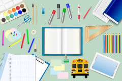 School supplies are lying around the open book. On the green background. Free place for your text is in the open book Royalty Free Stock Images