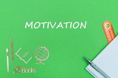 School supplies wooden miniatures and notebook with text motivation on green background. School supplies with notebook, ruler and pen on green background with Stock Images