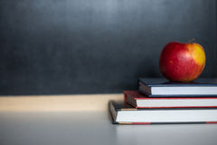 School supplies on old wooden table, near blackboard, close up Royalty Free Stock Photography