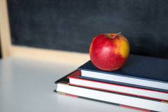 School supplies on old wooden table, near blackboard, close up Royalty Free Stock Images