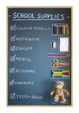 School supplies over blackboard background Royalty Free Stock Images