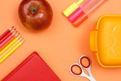 School supplies. Pencils, book, apple, scissors, felt pens and l. School supplies. Color pencils, red book, apple, scissors, felt pens and lunch box on pink royalty free stock image