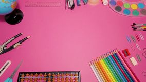 School supplies on pink board background. Education, back to school concept with copy space. Back to school expenses concept stock video footage