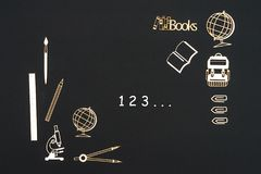 School supplies placed on black background with numbers 123. Concept back to school, numbers 123 with school supplies chipboard miniatures placed on blackboard Royalty Free Stock Images