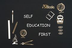 School supplies placed on black background with text self education first. Concept back to school, text self education first with school supplies chipboard Stock Images