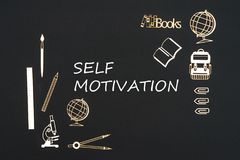 School supplies placed on black background with text self motivation. Concept back to school, text self motivation with school supplies chipboard miniatures Royalty Free Stock Photos