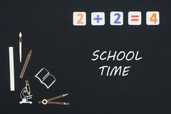 School supplies placed on black background with text school time. Concept first class school, text school time with wooden miniatures school supplies and Royalty Free Stock Photo