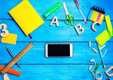 School supplies in the school desk with a phone in the center. Stationery, school concept, blue background, creative chaos, markers, pens, notepads, stickers Royalty Free Stock Images
