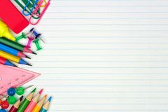 School supplies side border on lined paper background. Colorful school supplies side border over a lined paper background Royalty Free Stock Photo
