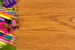 School supplies side border on wood desk Royalty Free Stock Photos