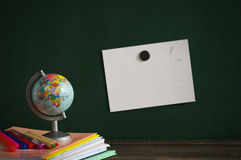 School supplies and the small globe against a blackboard. Notebooks, handles, colored pencils and the globe on a wooden surface against a blackboard Stock Photos