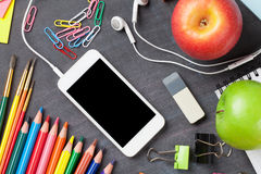 School supplies and smartphone on blackboard background Royalty Free Stock Images