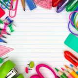 School supplies square frame on lined paper background. Colorful school supplies square frame over a lined paper background Stock Images