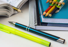 School supplies, stationery, multicolored pencils, pen, highlighter, opened math workbook on white desktop, learning, studying Royalty Free Stock Image