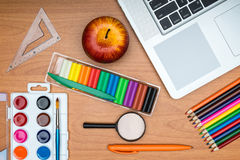 School supplies and tablet on wooden school desk from above Stock Photo