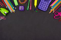 School supplies top border on chalkboard background royalty free stock image
