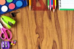 School supplies top corner border on a wooden desk background Royalty Free Stock Images