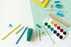 School supplies on white and blue checkered background royalty free stock photo