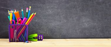 School supplies on a wood desk with chalkboard background. Back to school. Copy space. Banner. School supplies on a wood desk with chalkboard background. Side royalty free stock photos