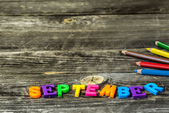 School supplies on wooden background, colorful pencils, with the word September Stock Photo