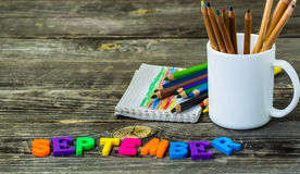 School supplies on wooden background, a mug of crayons and  Notepad, word September Royalty Free Stock Photos