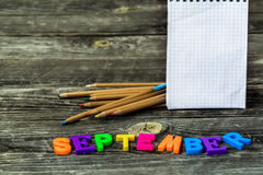 School supplies on wooden background, Notepad pencils with the word September Royalty Free Stock Images