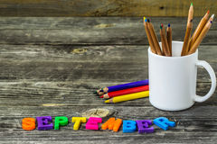 School supplies on wooden background, Notepad pencils with the word September Stock Photo