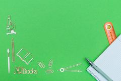 School supplies wooden miniatures and notebook with ruler and pen on green background. Concept school. Copy space Stock Image