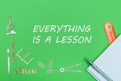 School supplies wooden miniatures and notebook with ruler and pen with text everything is lesson on green background. School supplies wooden miniatures, notebook Royalty Free Stock Image