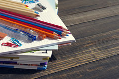 School supplies on a wooden old surface. Books, notebooks, handles, colored pencils on a wooden table Stock Image
