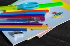 School supplies on a wooden old surface. Notebooks, handles, colored pencils on a wooden table Royalty Free Stock Images