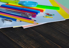 School supplies on a wooden old surface. Notebooks, handles, colored pencils on a wooden table Stock Image