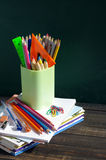 School supplies on a wooden surface against a blackboard. Books, notebooks, handles, colored pencils and rulers in a glass on a wooden table Royalty Free Stock Images