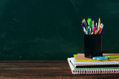 School supplies on a wooden surface against a blackboard. Royalty Free Stock Photography