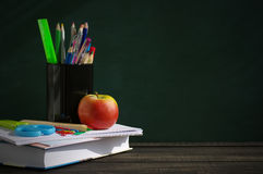 School supplies on a wooden surface against a blackboard. Books, notebooks, handles, colored pencils, rulers in a glass  and apple on a wooden table Royalty Free Stock Photography