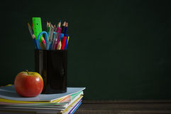 School supplies on a wooden surface against a blackboard. Books, notebooks, handles, colored pencils, rulers in a glass  and apple on a wooden table Stock Images