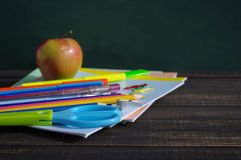 School supplies on a wooden table against a blackboard. Notebooks, handles, pencils, scissors and apple against a green blackboard Royalty Free Stock Photography