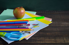 School supplies on a wooden table against a blackboard. Notebooks, handles, pencils, scissors and apple against a green blackboard Stock Photography