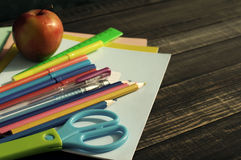 School supplies on a wooden table. Notebooks, handles, pencils, scissors and apple on a wooden table Stock Photography