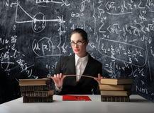 School teacher. Portrait of a school teacher sitting in front of a blackboard stock photography