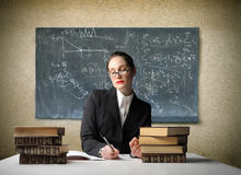 School teacher. Portrait of a school teacher sitting and writing in a classroom stock image