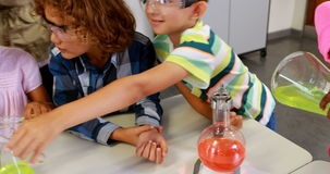 School teacher assisting school kids in chemical experiment in laboratory stock footage
