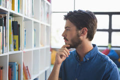 School teacher selecting book from bookshelf. In library at school Royalty Free Stock Photography