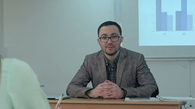 School teachers talk to a camera in a small school office. Professional shot in 4K resolution. 075. You can use it e.g. in your commercial video, business stock footage