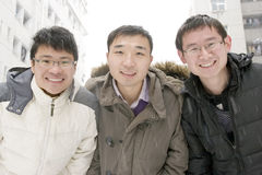 School team  in snow. Three young school man with coats smile in snow  day Royalty Free Stock Images