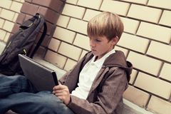 School teen with electronic tablet sitting Royalty Free Stock Photos